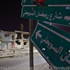 SIgn punctured by bullet holes marking Tripoli Street in downtown Misrata
