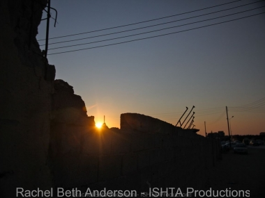 Sunset over remnants of buildings hit by rocket fire during battle