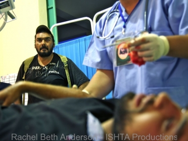 A fighter looks on as his friend is treated in a field hospital after being hit by shrapnel on the frontline