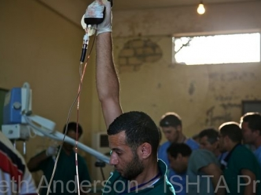 A volunteer nurse holds fluids inside a frontline field hospital as the doctors try to save a wounded fighter