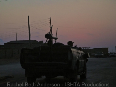 A stray car from a fighter convoy drives in the city at dusk