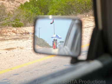 Side mirror view of checkpoint guards taking shade during the July summer heat