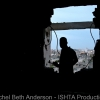 Silhouette of a fighter looking out of a mortar hole onto the city at dusk