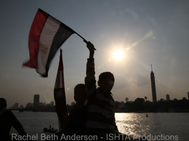 Waving Egyptian flag at sunset along the Nile
