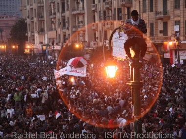 Praying atop light post in Tahrir