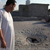 Looking at damage to roof after his families home was hit by rockets fired by Gaddafi forces