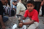 A child holds the unexploded casing of a rocket dug up from beneath a street after being fired by Gaddafi forces