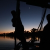Feluca captain steering on the Nile by Luxor at sunset