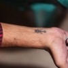 Tattoo artists shows his own Coptic Cross