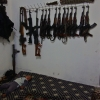 A child sleeps under weapons hung inside an FSA headquarters in the city of Taftanaz.
