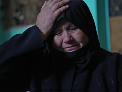 A women weeping for her three sons killed by government forces in a raid on Sarmeen.