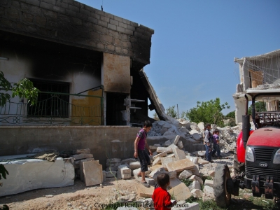 Children run through rubble of a home destroyed by tank shells in Kelly.